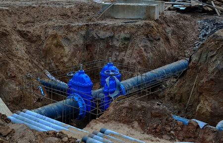 Photo pour Laying underground storm sewers at construction site, water main, sanitary sewer, drain systems.  Groundwater system for new residential buildings in the city. Ball valve background. Small sharpness - image libre de droit