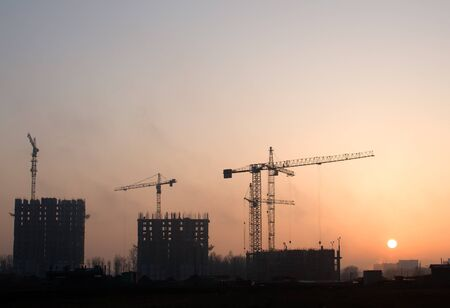 Photo for Silhouettes of tower cranes constructing a new residential building at a construction site against sunset background. Renovation program, development, concept of the buildings industry. - Royalty Free Image
