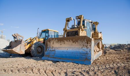 Photo pour Dozer working at construction site. Bulldozer for land clearing, grading, pool excavation, utility trenching and foundation digging. Crawler tractor and earth-moving equipment - image libre de droit