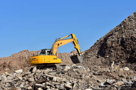 Photo for Yellow excavator at landfill for disposal of construction waste. Backhoe dig gravel at mining quarry on blue sky background. Recycling concrete and asphalt from demolition. - Royalty Free Image