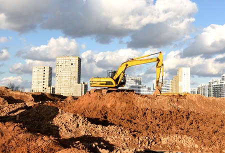 Photo pour Excavator during earthmoving at construction site. Backhoe dig ground for the construction of foundation and laying sewer pipes district heating. Earth-moving heavy equipment on road works - image libre de droit