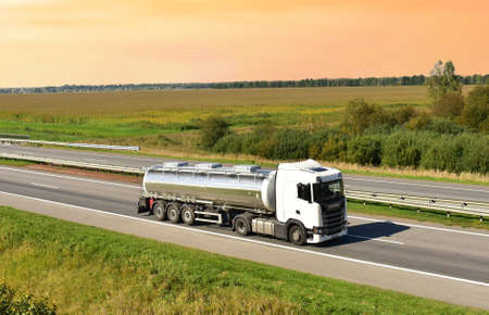 Isothermal Tank truck driving on highway. Oil and Gas Transportation and Logistics. Metal chrome cistern tanker with petrochemicals products. Liquid Chemical Freight