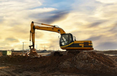 Photo for Excavator dig the trenches at a construction site. Trench for laying external sewer pipes. Sewage drainage system for a multi-story building. Digging the pit foundation. - Royalty Free Image