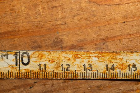 Old rusty ruler with black numbers on a working wooden table. vintage measuring tape. industrial background. carpentry workbench with copy space