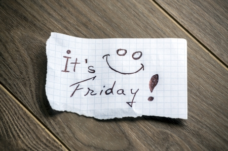 It's Friday - Hand writing text on a piece of paper on wood background
