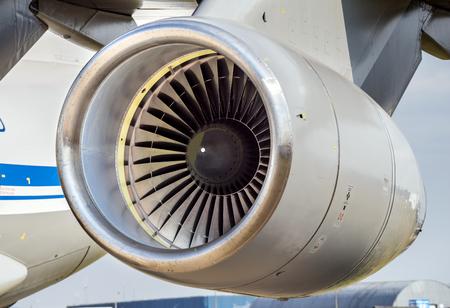 Engine turbine on fuselage of passenger plane, jet turbine and wing, aviation and aerospace industry on background blue sky