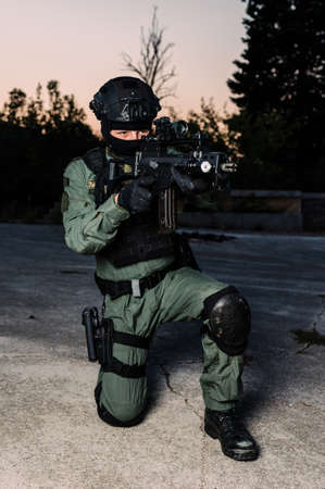 Photo for Man reenacting special unit of Croatian military police. Wearing green jumpsuit with black add-ons and assault rifle G36. - Royalty Free Image