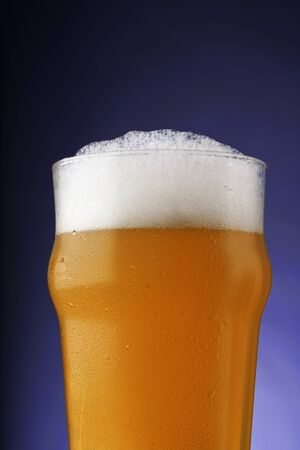 Photo pour A pint of beer with foam in a glass with water drops on a dark background with gradient lighting - image libre de droit