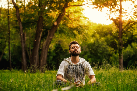 Photo pour A bearded man is meditating on green grass in the park with face raised up to sky and eyes closed on sunny summer day. Concept of meditation, dreaming, wellbeing and healthy lifestyle - image libre de droit
