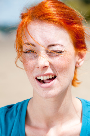 Closeup outdoor portrait of a young beautiful redhead woman winking