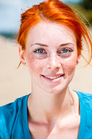 Portrait of a happy smiling beautiful young redhead woman with blue eyes and freckles