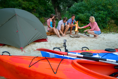 Young Happy Travelers Resting at the Evening with Fire on the Sand Beach near Kayaks and Tent. Travel, Adventure and Water Recreation Concept.