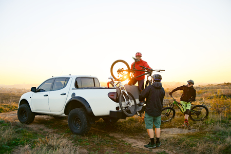 Photo pour Friends Taking MTB Bikes off the Pickup Offroad Truck in Mountains at Sunset. Adventure and Travel Concept. - image libre de droit