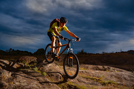 Photo for Cyclist Riding the Mountain Bike on Rocky Trail in the Evening. Extreme Sport and Enduro Biking Concept. - Royalty Free Image