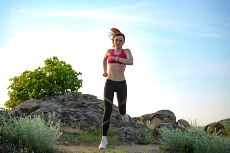 Photo for Young Beautiful Woman Running on the Mountain Trail in the Hot Summer Evening. Sport and Active Lifestyle. - Royalty Free Image