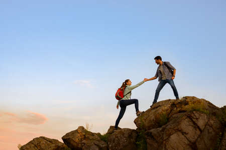 Photo pour Travelers Hiking in the Mountains at Sunset. Man Helping Woman to Climb to the Top. Family Travel and Adventure. - image libre de droit