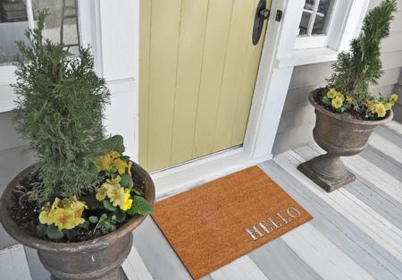 Foto de Classic beige and Silver zute / coir Outdoor Door mat with Hello text outside home with yellow flower pots - Imagen libre de derechos