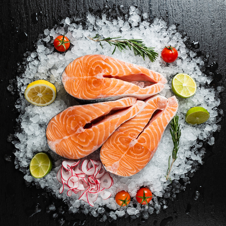 Photo for Slice of red fish salmon with lime, rosemary and  radish on the ice - Royalty Free Image