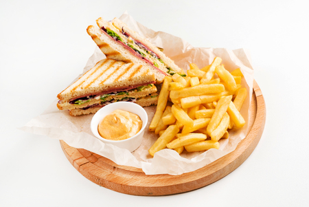 Foto de Club Sandwich with Cheese, PIckled Cucmber, Tomato and Smoked Meat. Garnished with French Fries - Imagen libre de derechos