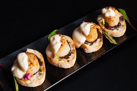 Photo pour scallop appetizers with sauce on the black background - image libre de droit