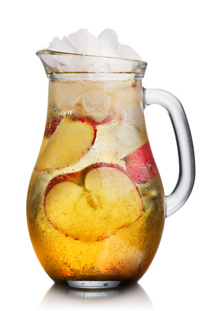 Glass pitcher of homemade spritzer (apfleschorle) served with crushed ice and apple slices. Jug full of non-alcoholic sparkling and cold carbonated apple juice.