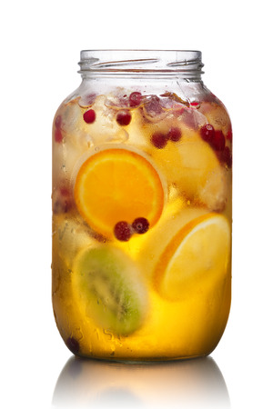 Glass jar of homemade spritzer (schorle) with carbonated apple juice served with frozen fruit wheels, ice cubes and wild cranberry
