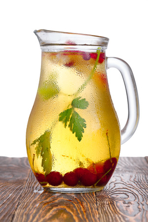 Glass pitcher of homemade spritzer (schorle) enriched with cherries and apple slices. Jug full of non-alcoholic sparkling and cold carbonated juice.