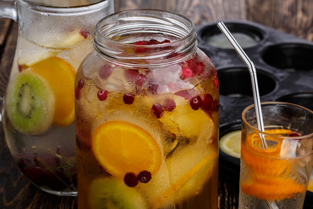 Homemade party soft drinks in jars and jugs on wooden table. Bulk spritzer beverages. Selective focus