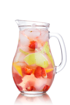 Glass jug of iced detox water with strawberry, apple and lemon