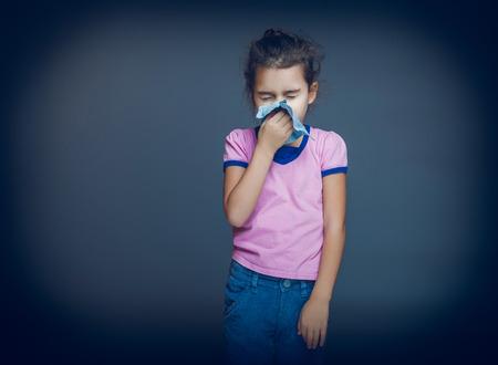Teenage girl suffers a handkerchief on gray background cross p