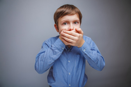 boy in a shirt covered fright mouth with her hands
