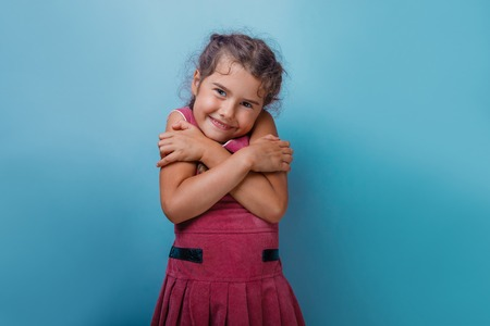Girl European appearance decade hugging herself on a blue  background
