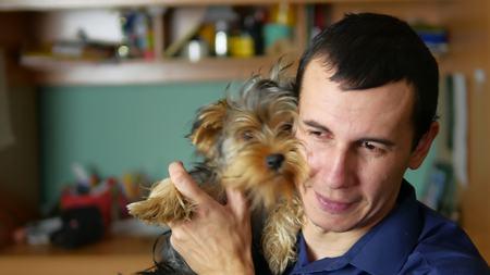 man embraces and kisses dog pet friendship