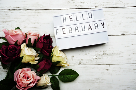 Photo pour Hello February Word on Light box with roses flower bouquet on wooden background - image libre de droit