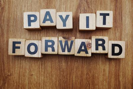 Photo pour Pay It Forward alphabet letter on wooden background - image libre de droit