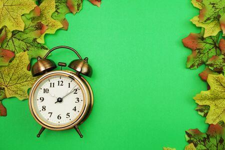 Photo pour Alarm clock with Maple leaf border on green background - image libre de droit