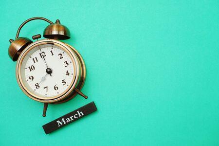 Photo pour Alarm clock and March calendar with space copy on green mint background - image libre de droit