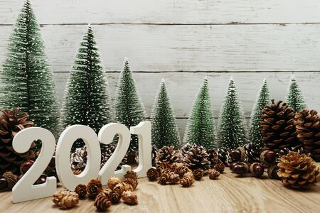 Photo for Happy New Year 2021 festive background with christmas tree and pine cone decoration on wooden background - Royalty Free Image