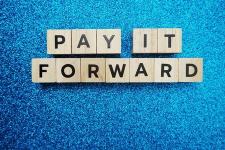 Photo pour Pay It Forward alphabet letter on blue glitter background - image libre de droit
