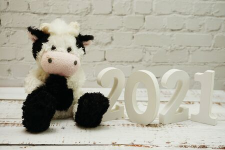 Photo pour 2021 Happy New Year and Cute Funny cow doll with space copy on white brick wall and wooden background - image libre de droit