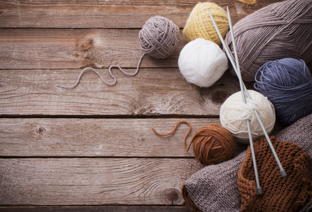 Foto de Knitting and knitting needles on a wooden surface - Imagen libre de derechos