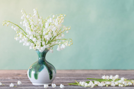 Foto de Lilly of valley in  vase on wooden table - Imagen libre de derechos