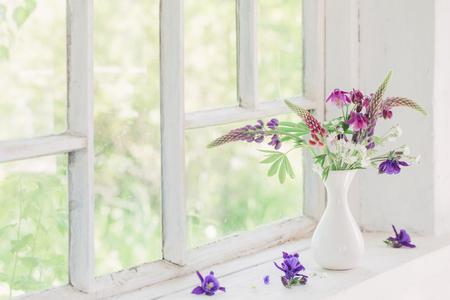 Photo pour summer flowers in vase on white windowsill - image libre de droit