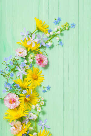 Photo for frame of beautiful flowers on green wooden background - Royalty Free Image