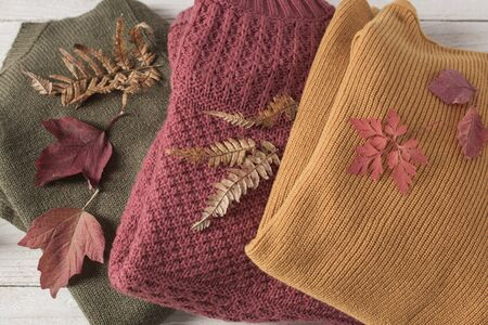 Photo pour stack of sweaters with autumn leaves  on  white wooden table - image libre de droit