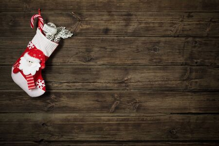 Photo pour Christmas stocking with gifts hanging on dark old wooden background - image libre de droit