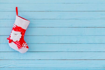 Photo pour Christmas stocking with gifts hanging on blue wooden background - image libre de droit