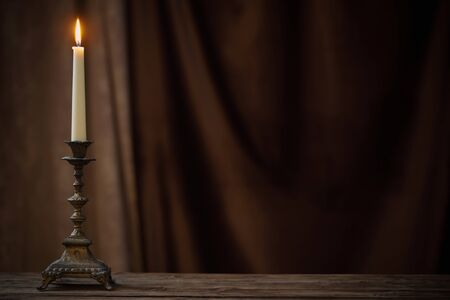 Photo for antique candlestick with burning candle on old wooden table on background brown velvet curtain - Royalty Free Image