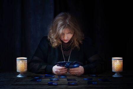 Photo pour mature woman guessing with cards on dark background - image libre de droit