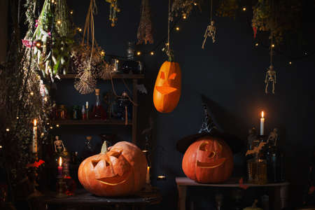 Foto de Halloween pumpkins with lights and burning candles and magic potions in witch's house - Imagen libre de derechos
